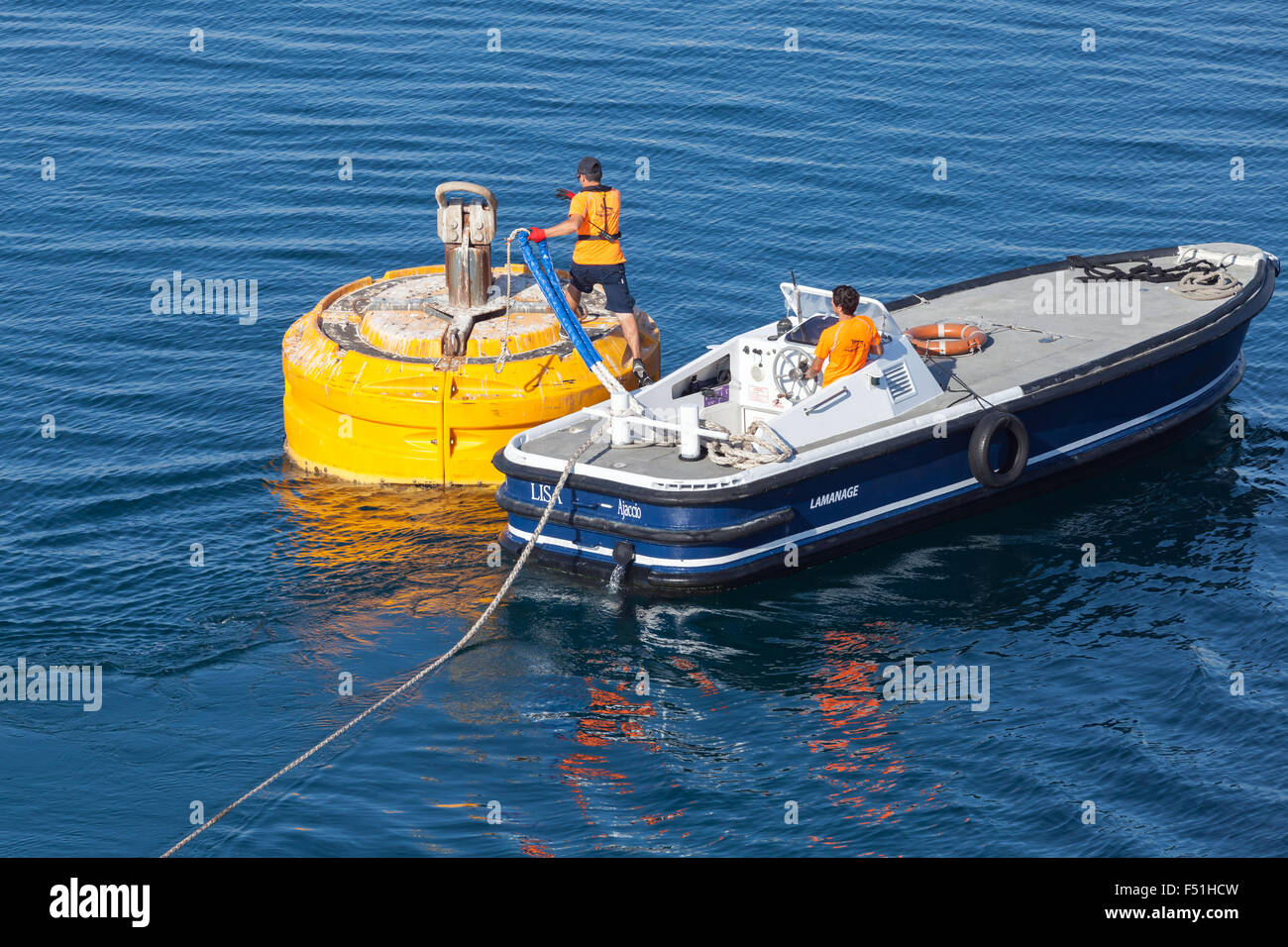 Ajaccio, France - June 30, 2015: Port operations, men at work. Motorboat is used for rope attachment on yellow mooring - Stock Image