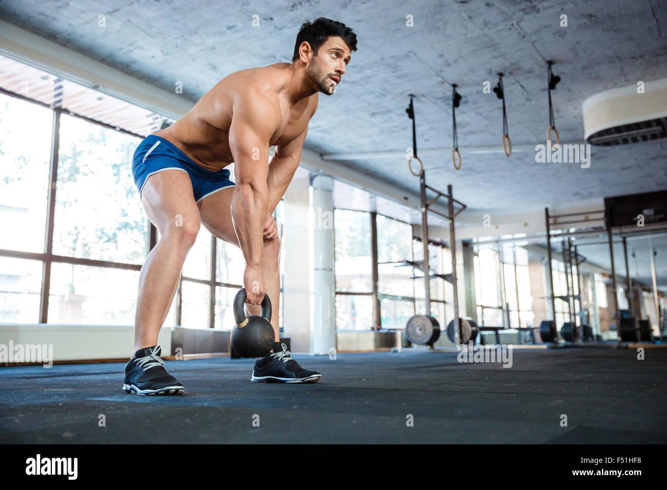 Beautiful athlet wearing blue shorts lifting kettle ball - Stock Image