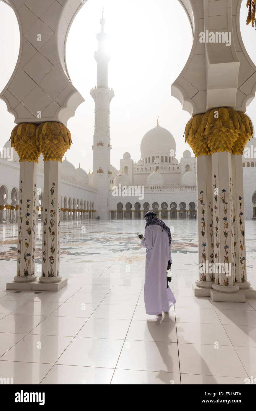 Man in thawb and gutra between the pillars lined up around the central square of the Sheikh Zayed Grand Mosque in - Stock Image