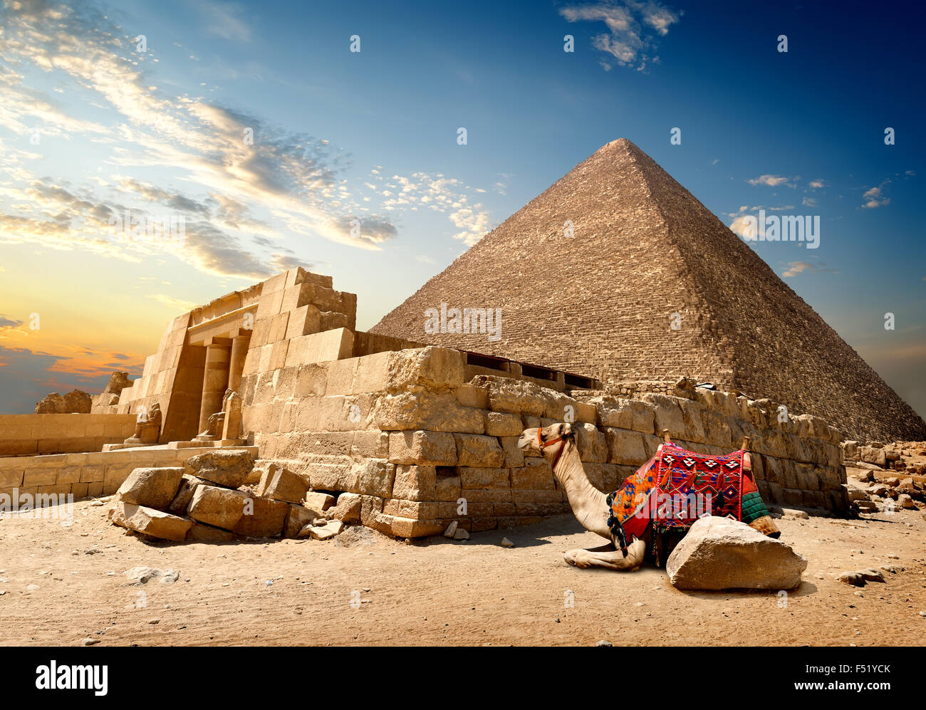 Camel rests near ruins of entrance to pyramid - Stock Image