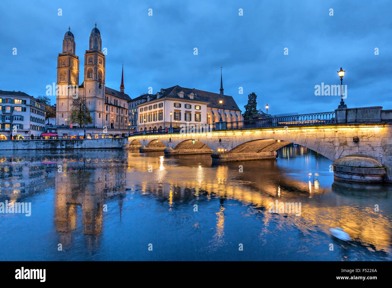 Munsterbrucke and Grossmunster church reflecting in river Limmat, Zurich, Switzerland - Stock Image