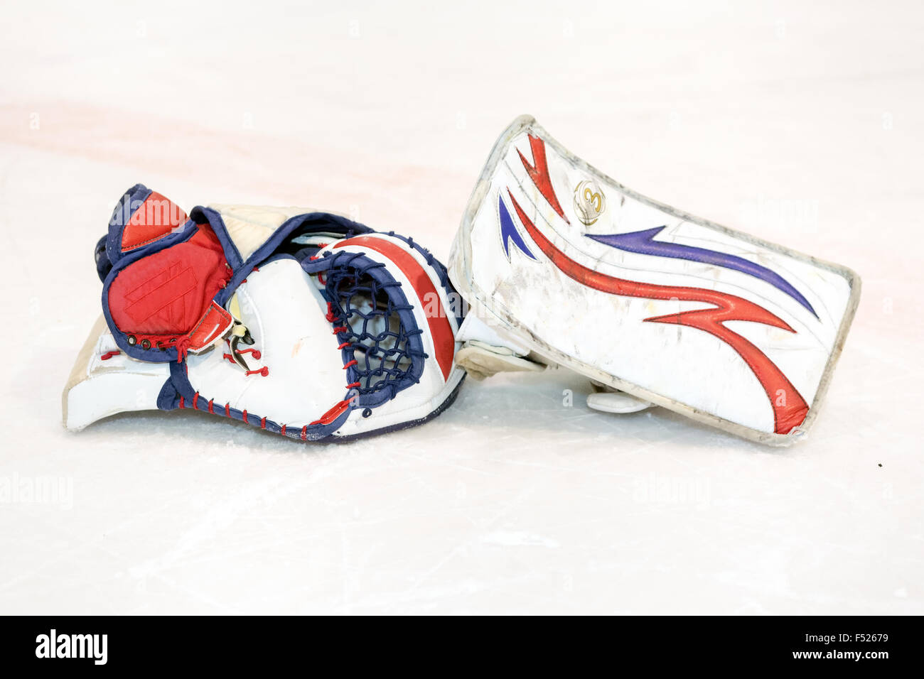 White goalkeeper gloves discarded on the ice - Stock Image