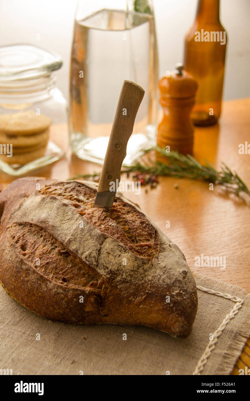 Fresh rustic bread loaf on the kitchen table with knife and kitchen utensils - Stock Image