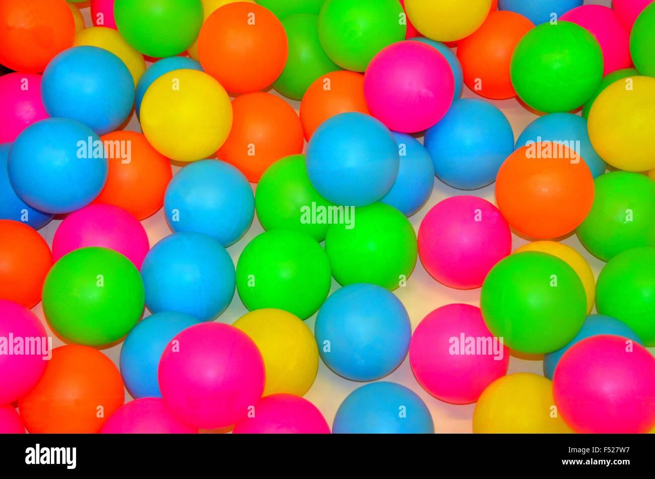 Vivid bright neon pink, orange, yellow, green and blue balls - Stock Image