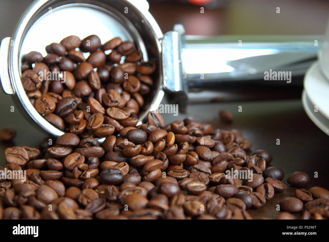 Coffee measuring spoon.Coffee beans spill out of the dimensional, metal spoons and lie loose on the table. - Stock Image
