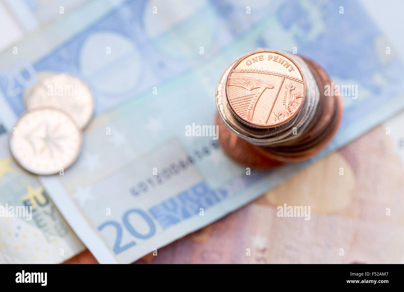 British one penny coin on a pile of coins and 20 Euro note Stock Photo
