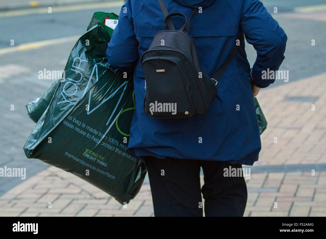 Shopper with purchases from Marks & Spencers,, M&S Female fashions in Church Street, Blackpool, Lancashire, - Stock Image