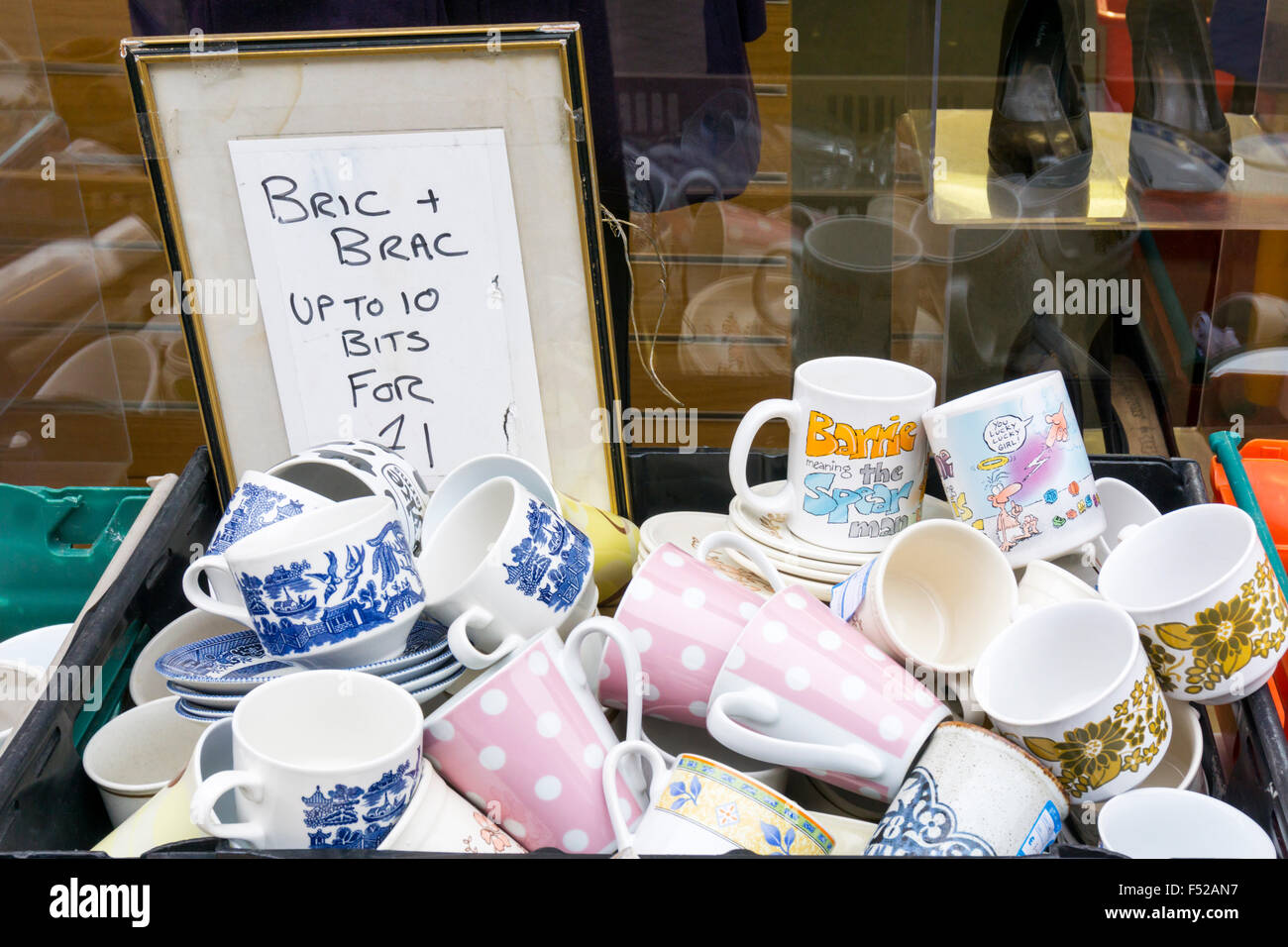 A box of secondhand crockery mugs and cups for sale outside a bric a brac shop. - Stock Image