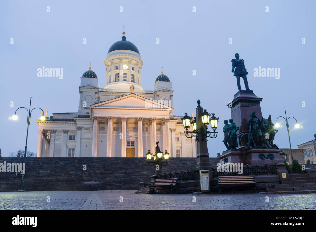 Lighted Lutheran Cathedral and statue of Tsar Alexander II at dusk. Senate square, Helsinki, Finland - Stock Image