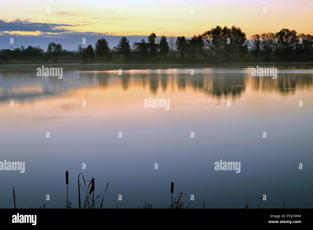 Sunrise landscape with a lake and the mist over the water - Stock Image