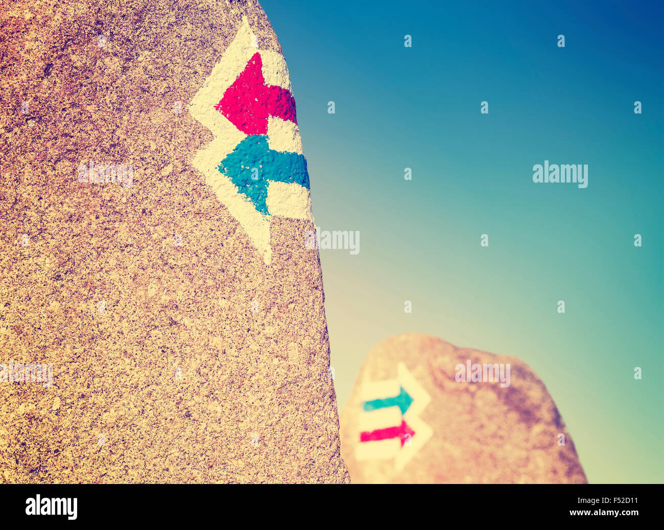 Vintage toned trail signs painted on rock, choice or dilemma concept. - Stock Image