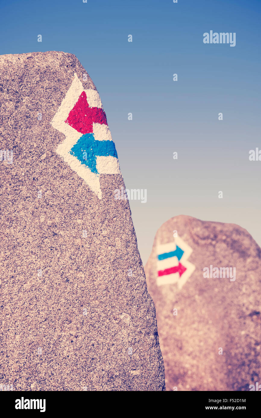 Retro toned trail signs painted on rock, choice or dilemma concept. - Stock Image