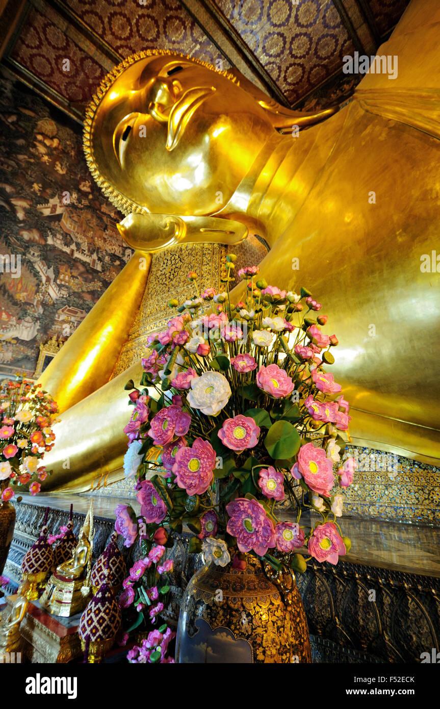 Reclining Buddha statue and flowers at Wat Pho (Wat Phra Chetuphon), Bangkok, Thailand - Stock Image