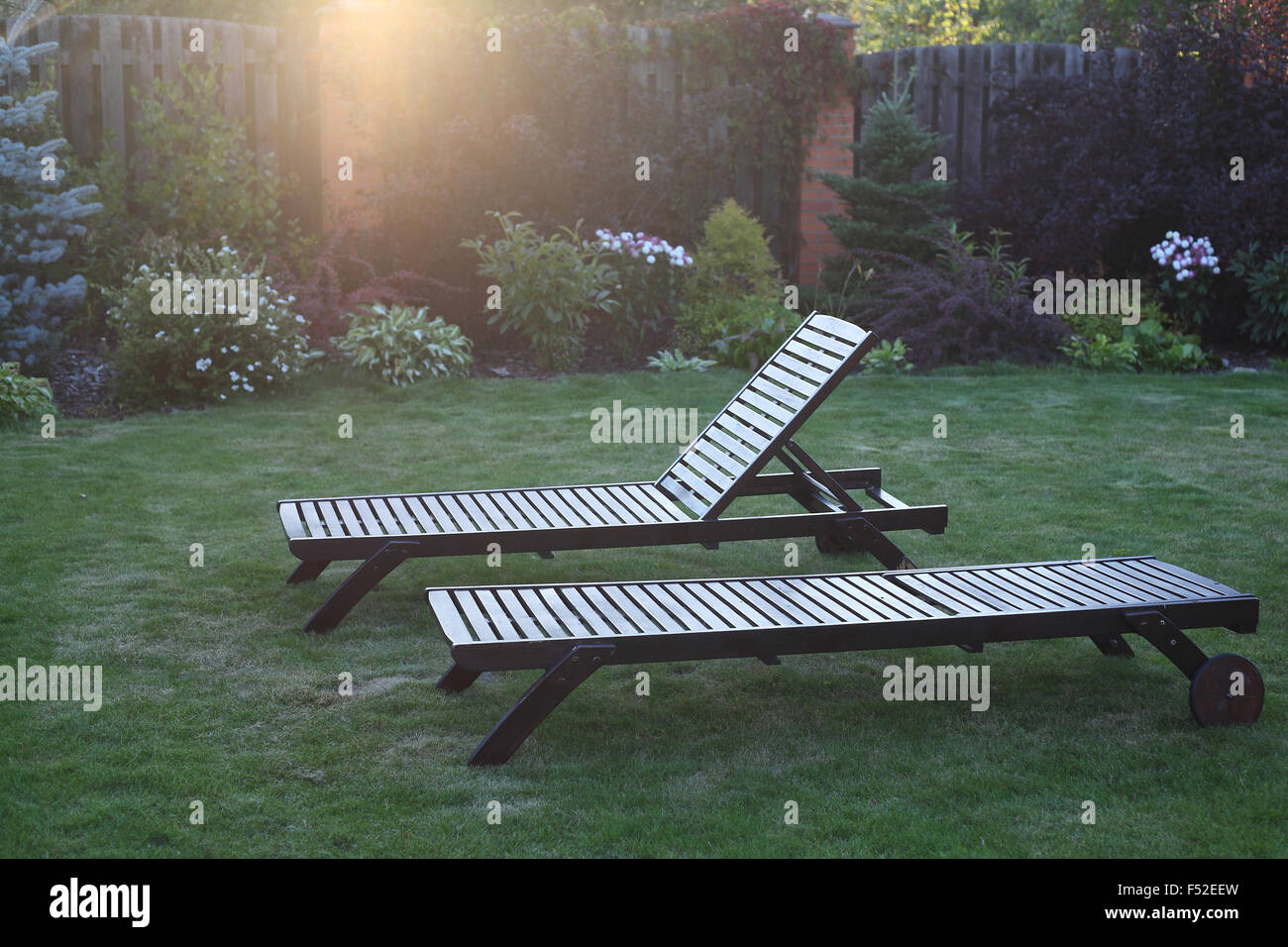 Two wooden chaise lounges in beams of the setting sun. - Stock Image