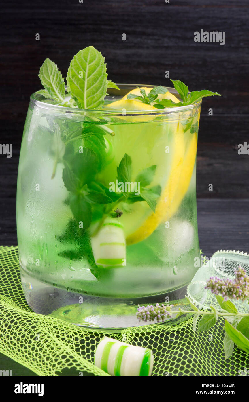 Homemade mojito cocktail in a crooked glass with mint bonbons - Stock Image