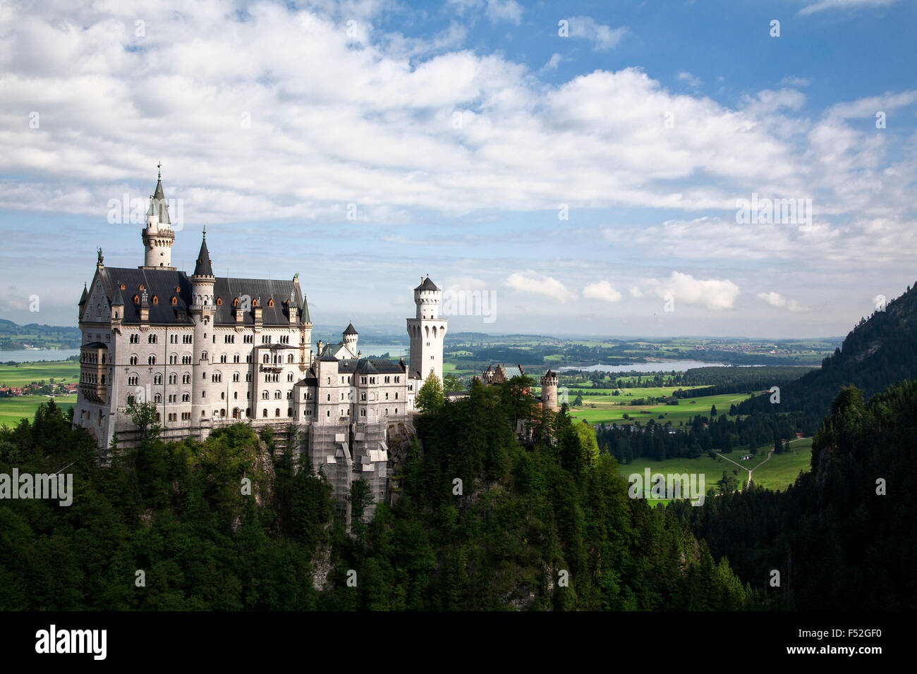 Neuschwanstein Castle overlooks the rolling hills in Bavaria, Germany. Stock Photo