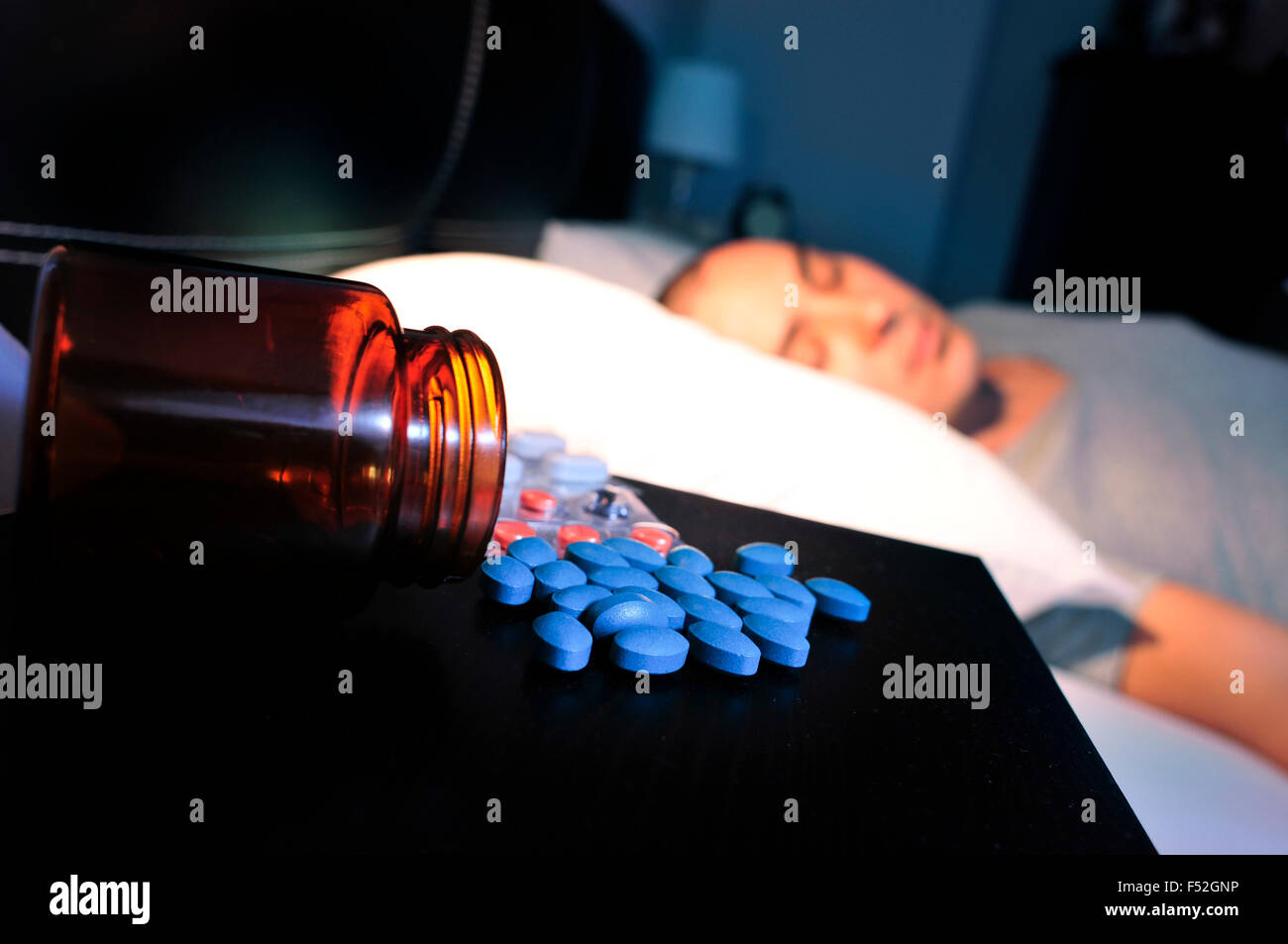 closeup of some different pills in the nightstand and a young man laying in bed with his eyes closed, at night - Stock Image