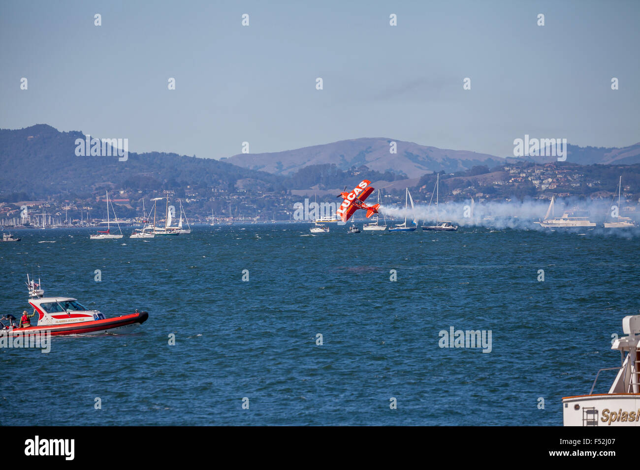 Lucas Oil pitts plane performing flight demonstration over San Francisco waterfront, San Francisco, California, - Stock Image