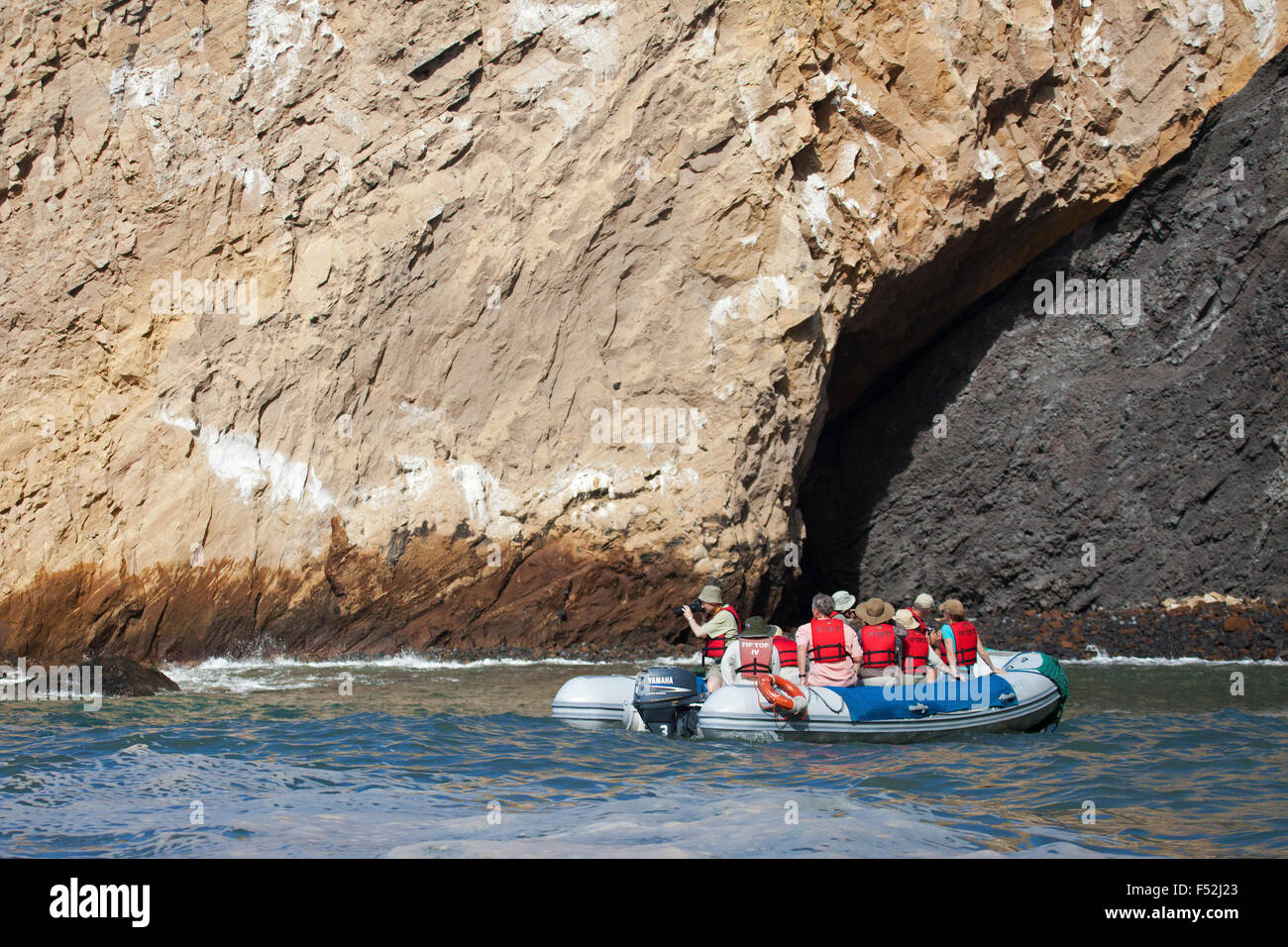 Tourists in dinghy viewing geological contact between tuff (compacted volcanic ash) and the darker scoria (cinder) - Stock Image