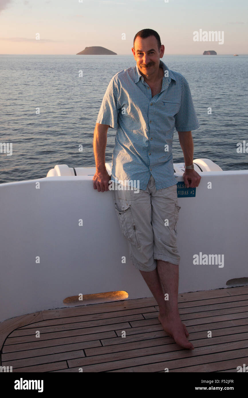 Tourist relaxing on Galapagos cruise. Daphne Major and Daphne Minor islands are in in the background - Stock Image