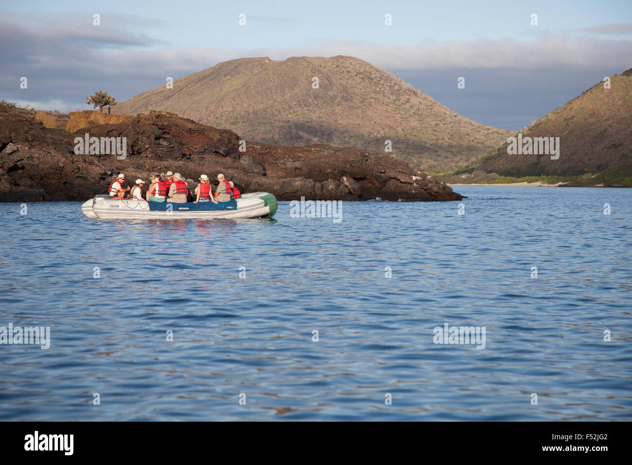 Tourists viewing volcanic landscape from panga - Stock Image
