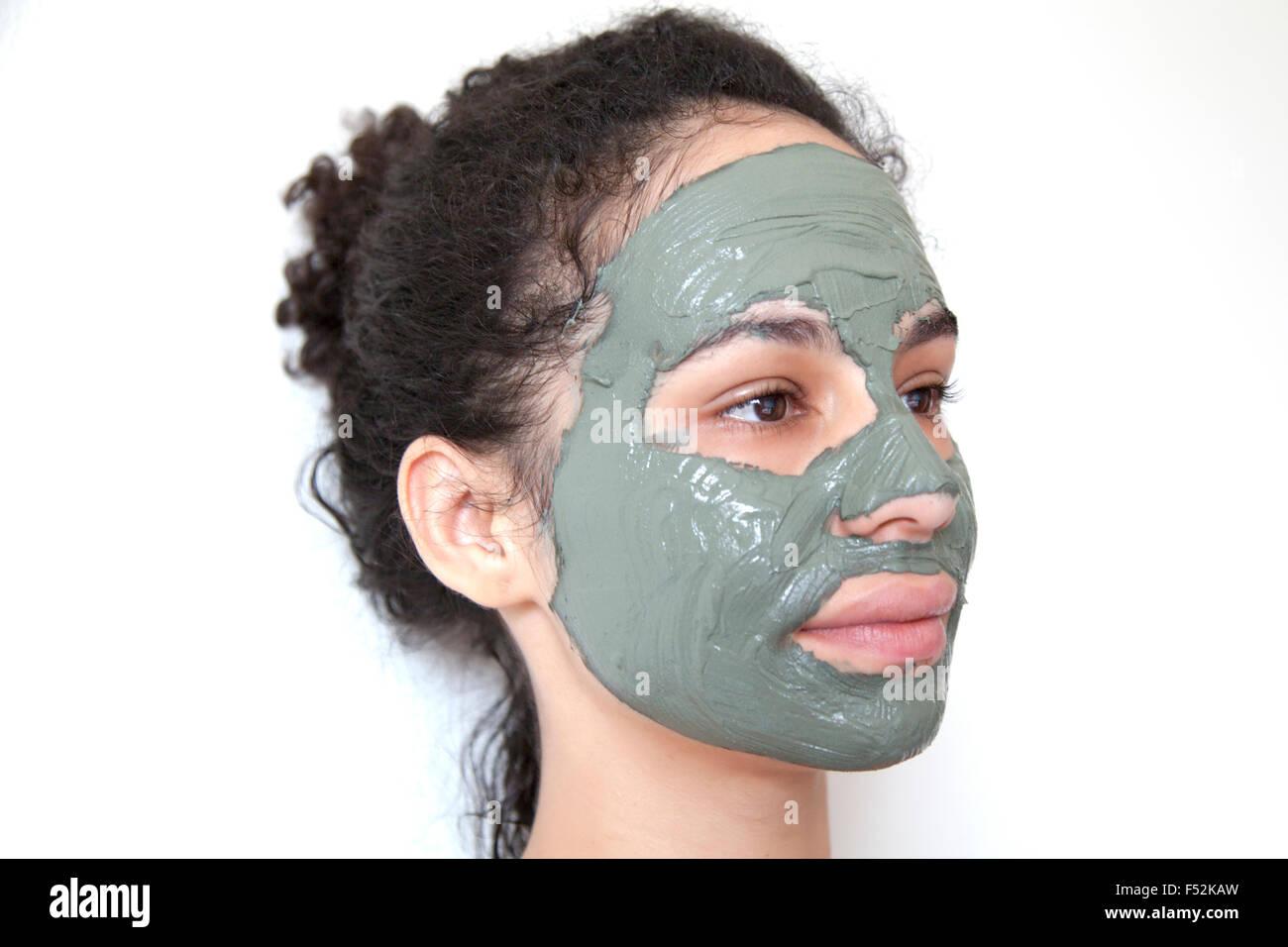 beautiful young brazilian model with green clay facial mask. spa