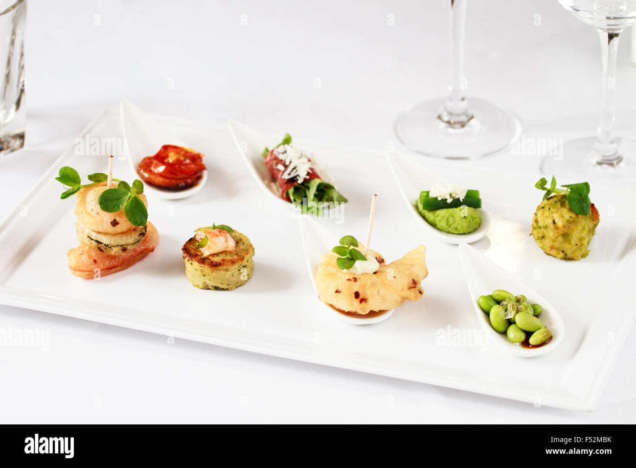 A platter with a selection of Canapes on white - Stock Image