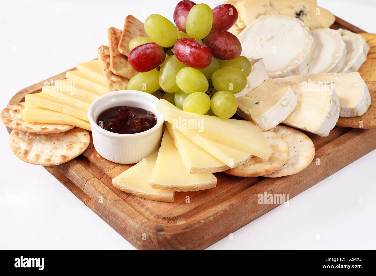 A platter of different cheese with grapes, biscuits, and raspberry jam on a wooden board isolated on White - Stock Image