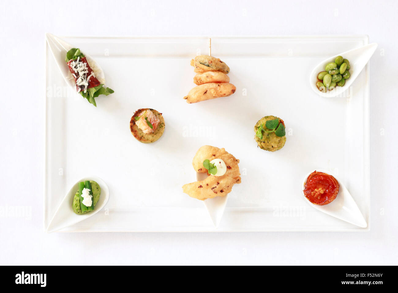 A top view of a platter with a selection of Canapes, isolated on white - Stock Image
