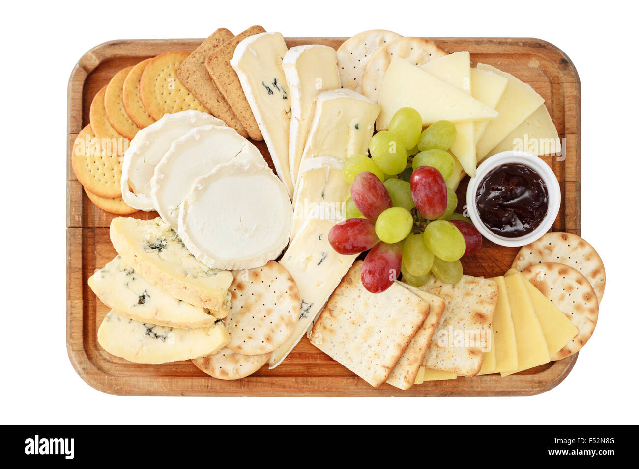Top view of a platter of different cheese with grapes, biscuits, and raspberry jam on a wooden board isolated on - Stock Image