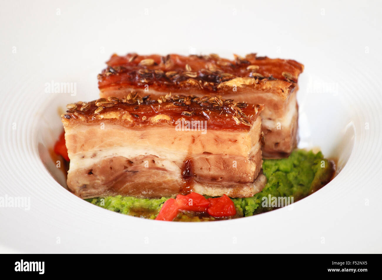 Spiced pork belly with Crushed peas & smoked red peppers - Stock Image
