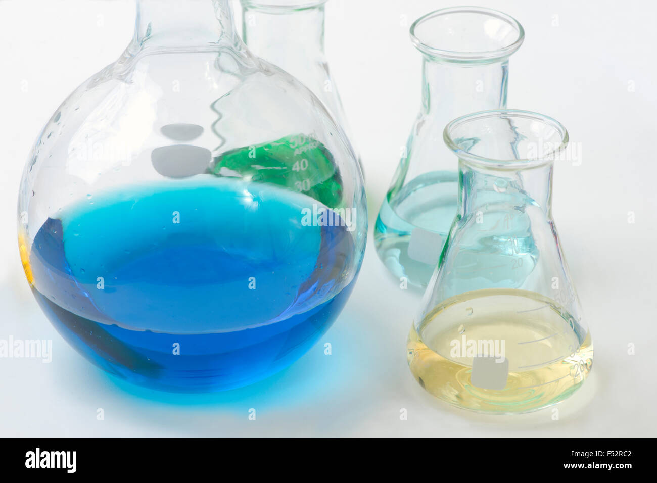 Different colored reagents in assorted laboratory flasks. Stock Photo