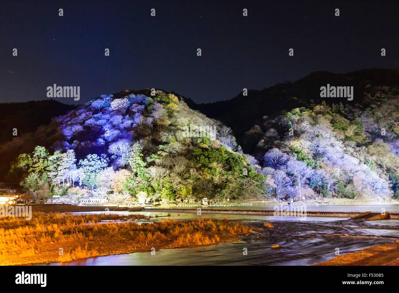Japan, Kyoto, Arashiyama. Hanatouro light festival. Night-time. View across Hozu River to tree covered mountain - Stock Image