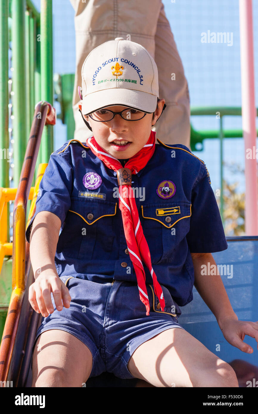 Japan. Japanese school boy scout, 8-10 years old, sliding down on playground slide at school, tentively and nervous - Stock Image