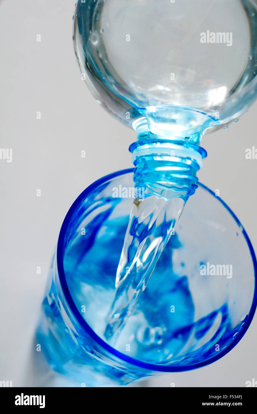 Water out of Bottle into Glass - Stock Image