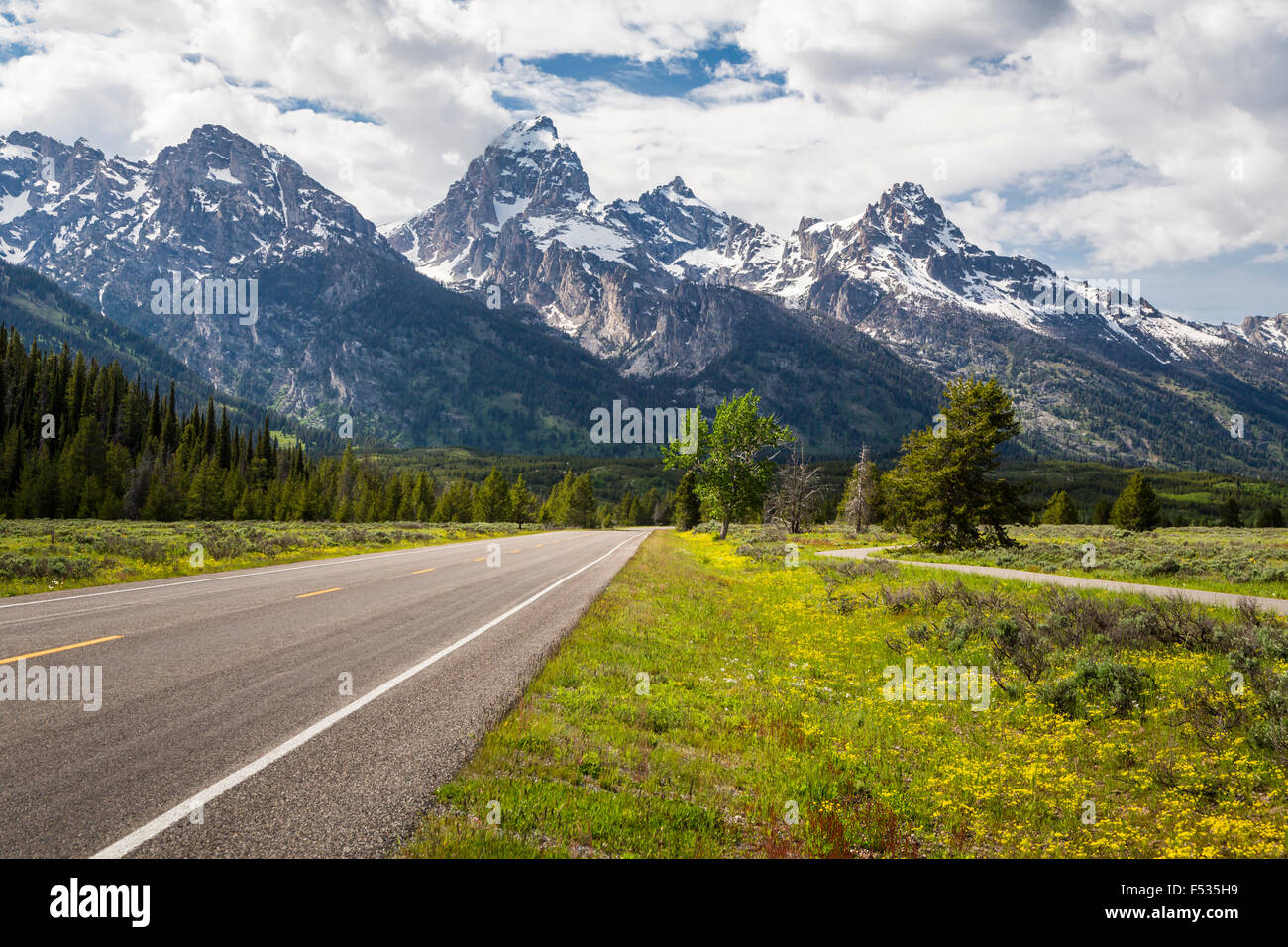 Mountains and a park roadway in the Grand Tetons National Park, Wyoming, USA. - Stock Image