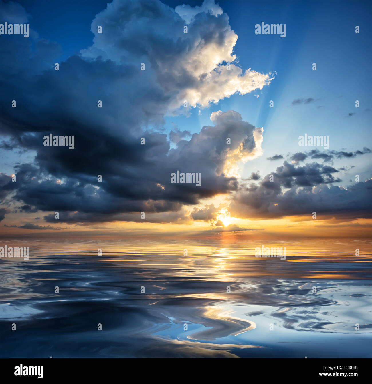 Dramatic sunset sky reflected in the water - Stock Image