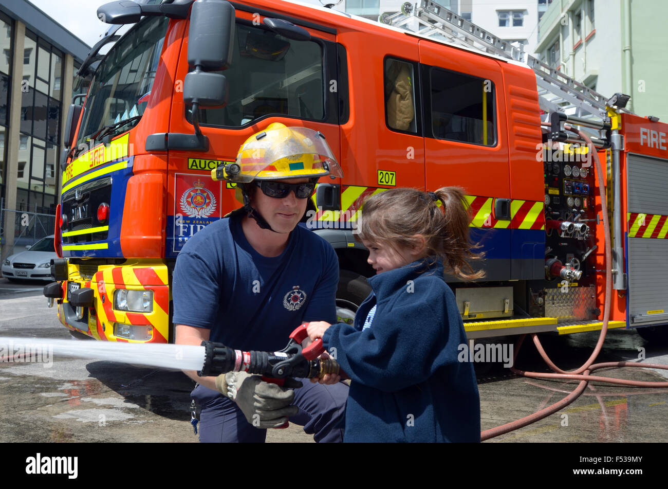 AUCKLAND  - OCT 27 2015:Firefighter and child (Talya Ben-Ari age 05) during Fire Safety Education day.Each year - Stock Image