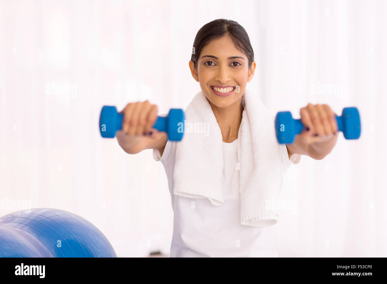 cheerful Indian woman working out with dumbbells - Stock Image