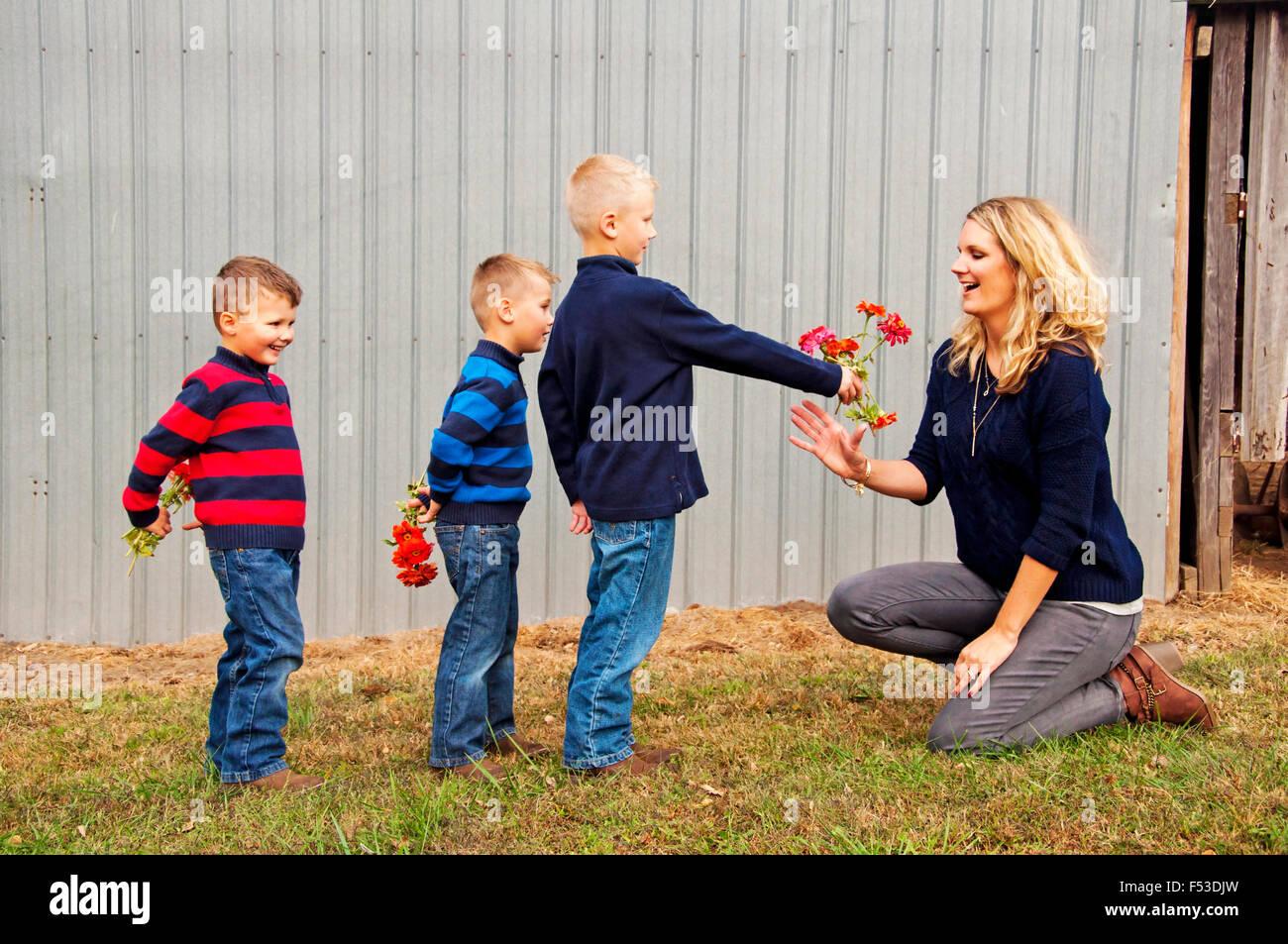 Boys giving mum flowers - Stock Image
