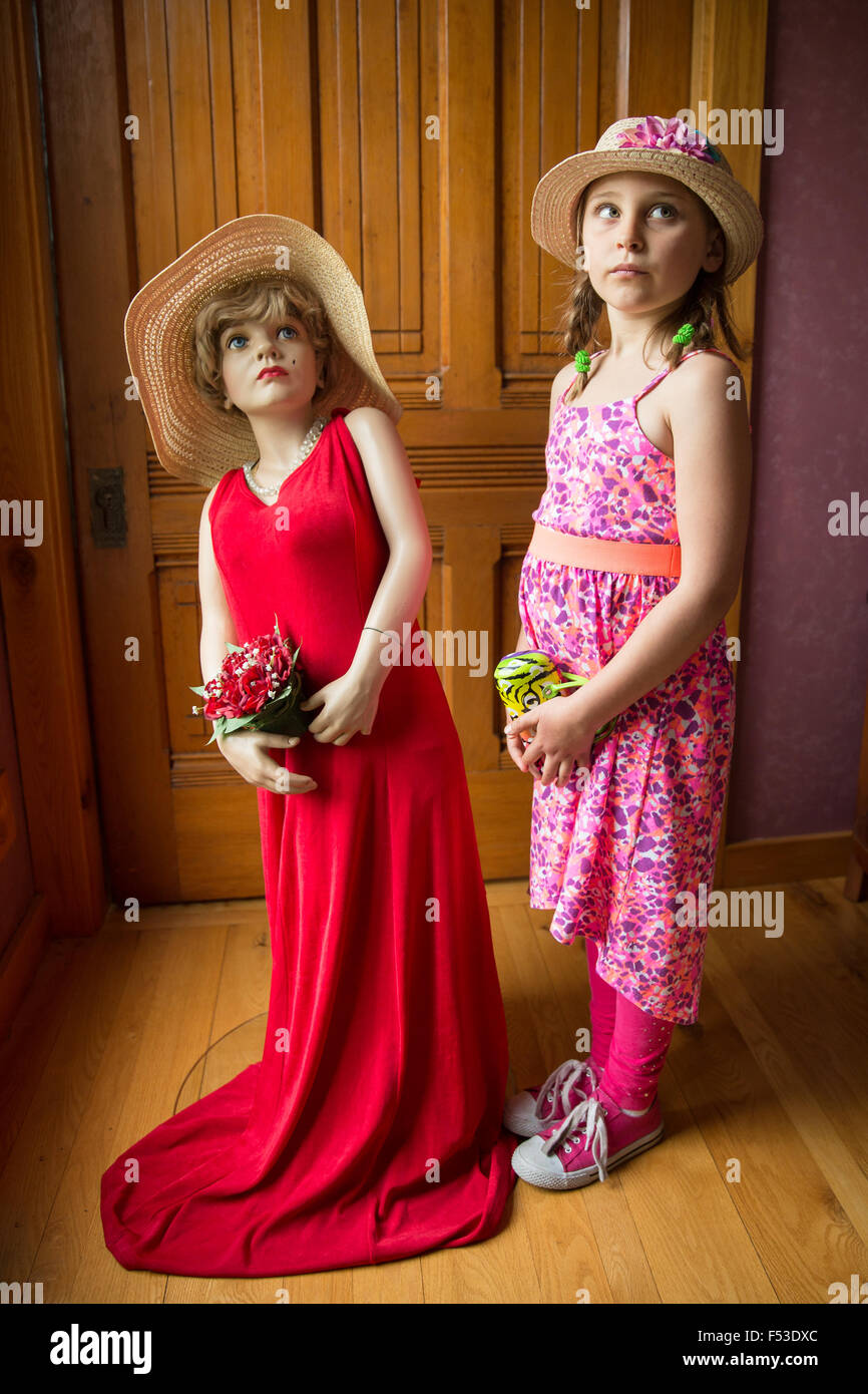 Young girl in a hat posing with mannequin wearing a red dress and hat.  Soft lighting and focus and warm vintage - Stock Image