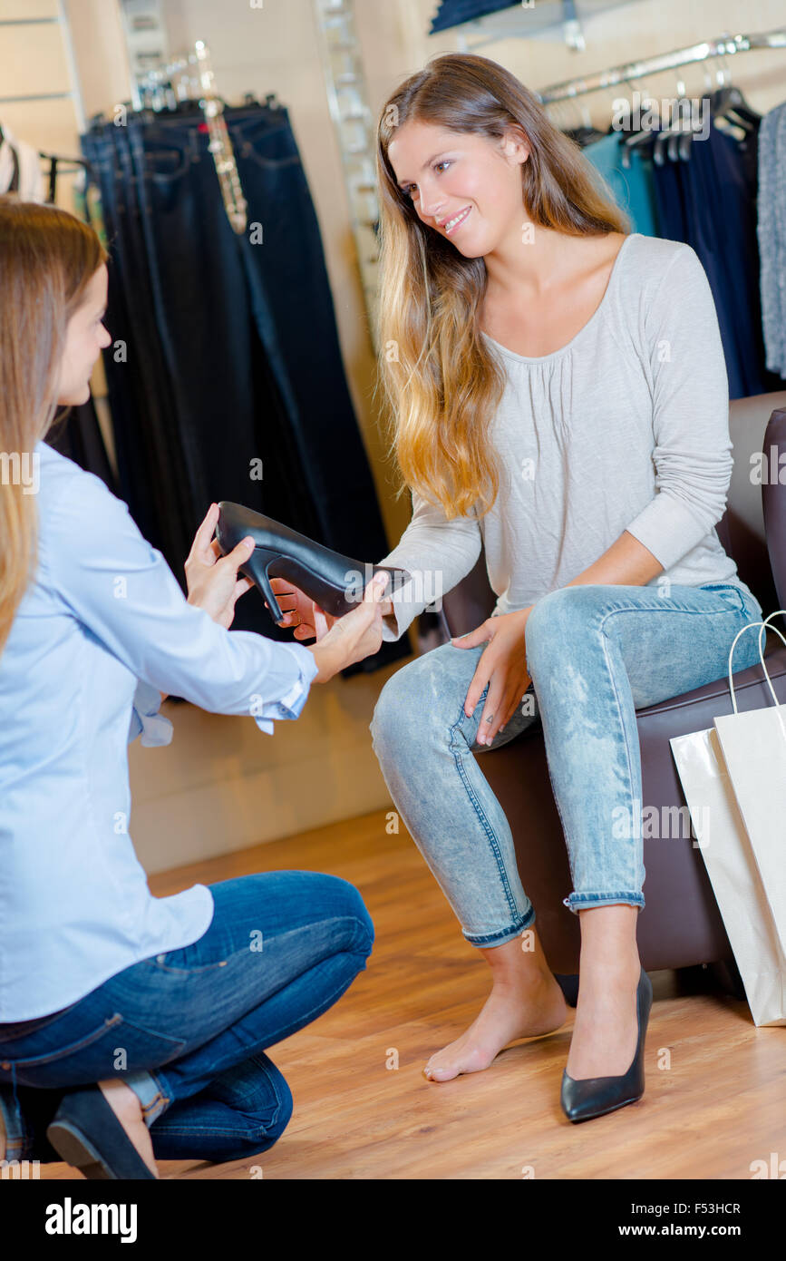 Sales assistant in a shoe shop - Stock Image