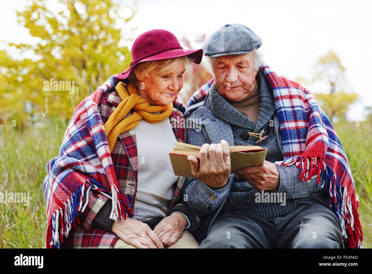 Concentrated senior couple reading interesting book outdoors - Stock Image