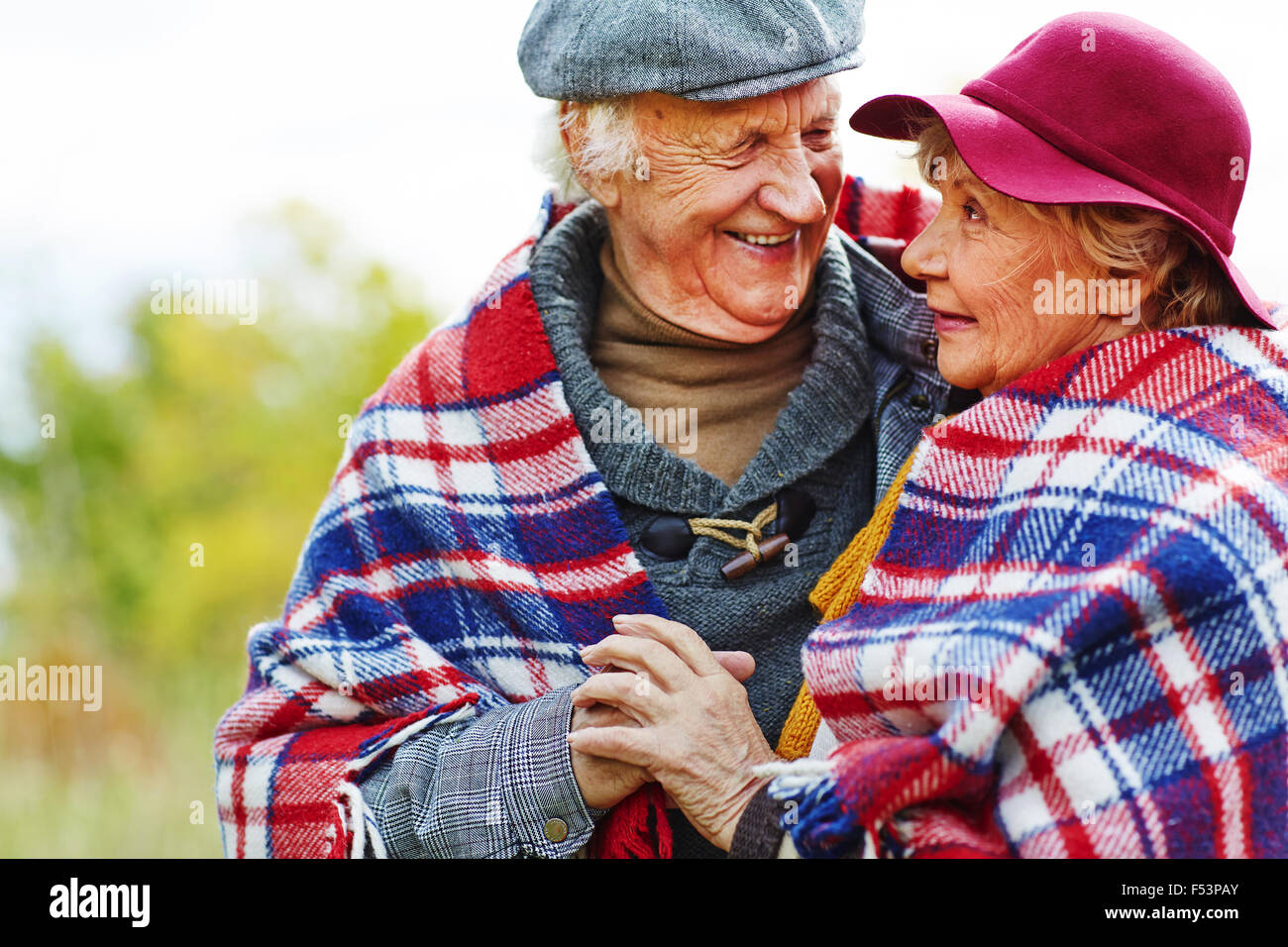 Senior couple wrapped with blanket remembering their youth - Stock Image