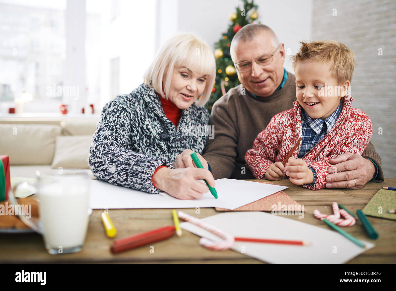 Little boy painting with grandpa and grandma - Stock Image