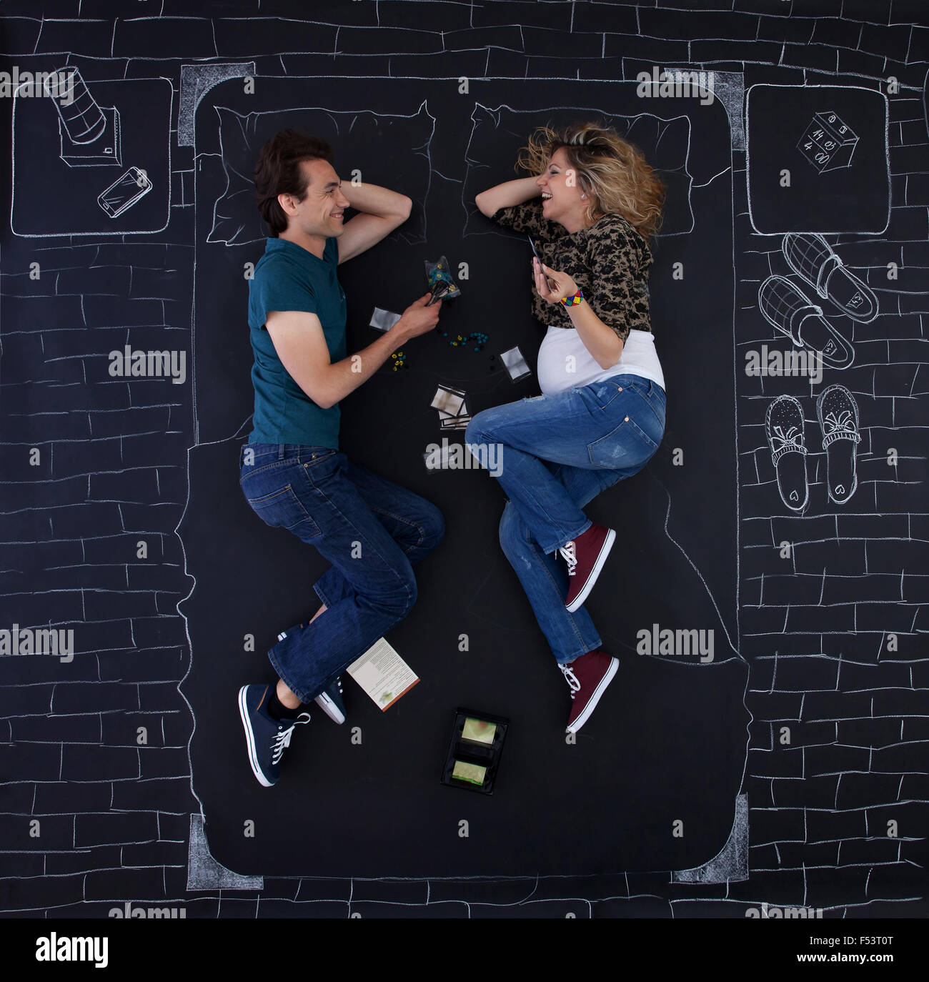 Young couple playing a board game in a bed drawed with chalk on paper. - Stock Image