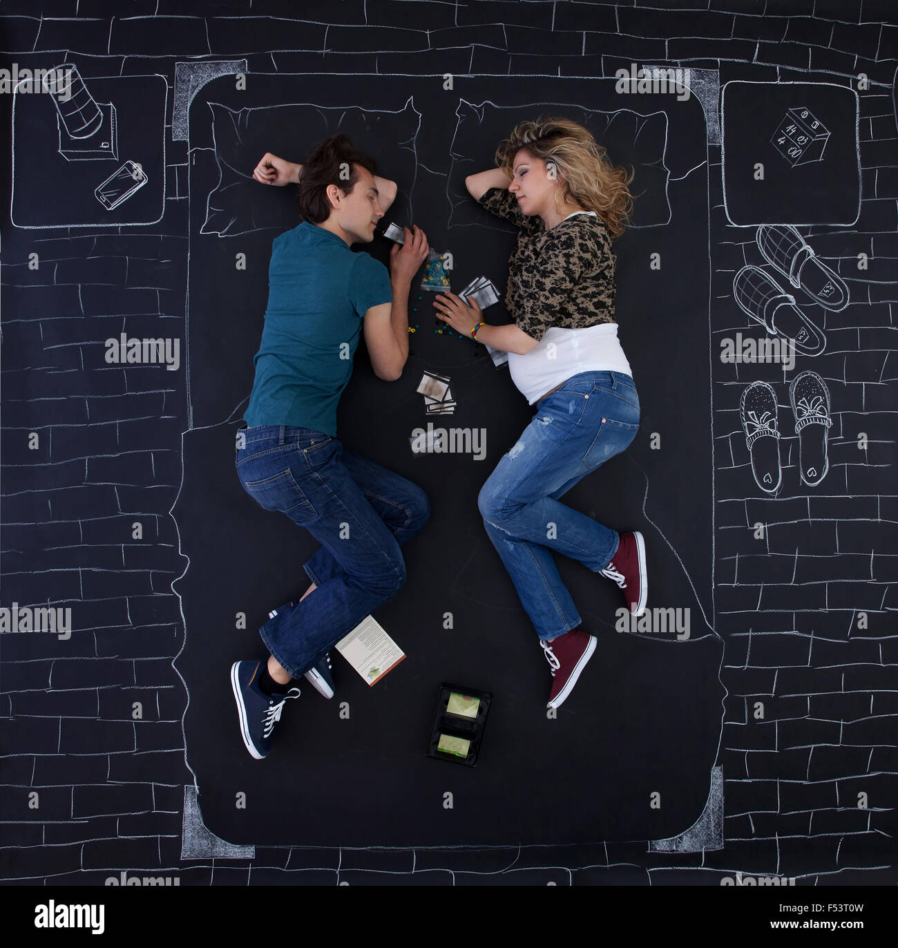 Young couple falling asleep while playing a board game in a bedroom drawed with chalk on paper. - Stock Image