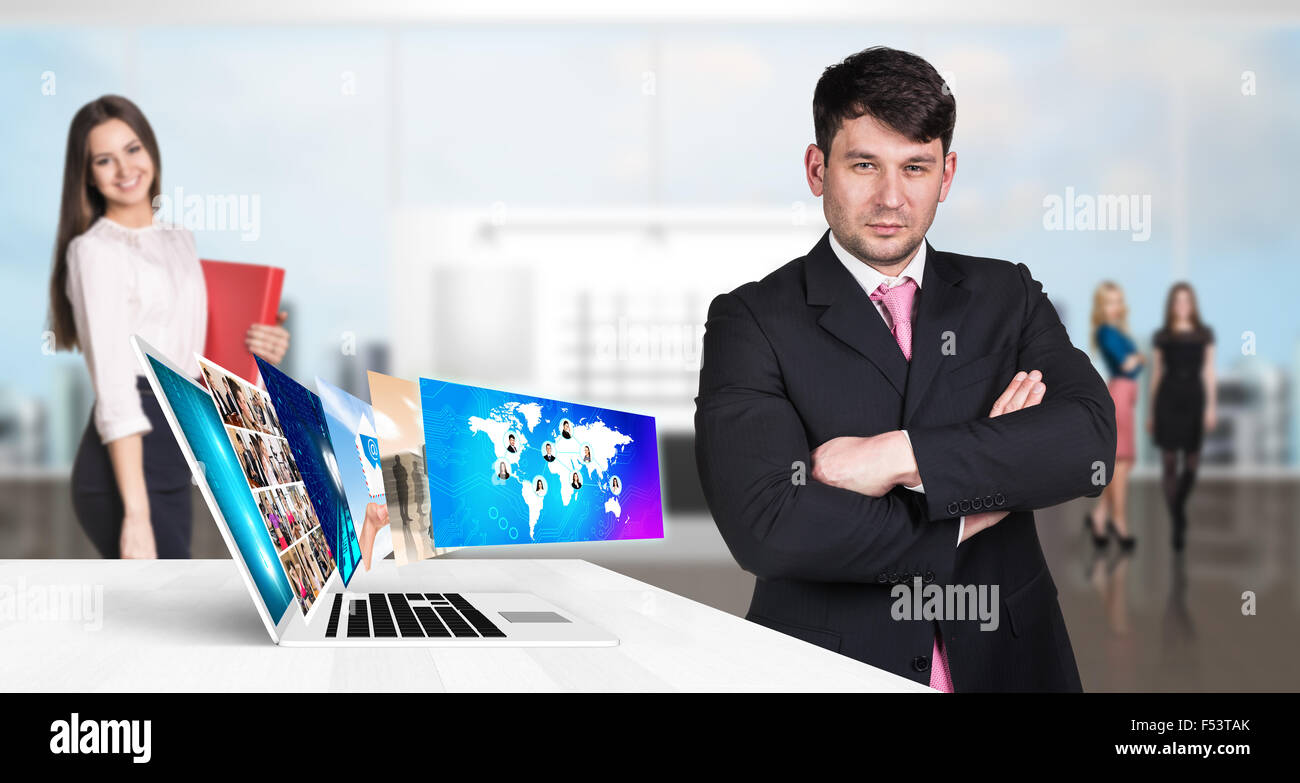 Businessman stands near laptop with many screens. Stock Photo