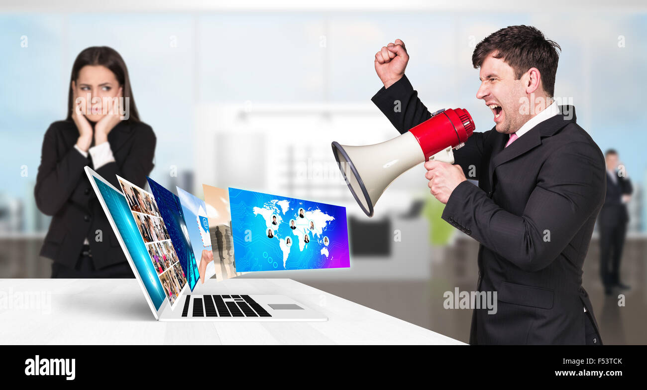 Businessman stands near laptop with many screens. - Stock Image