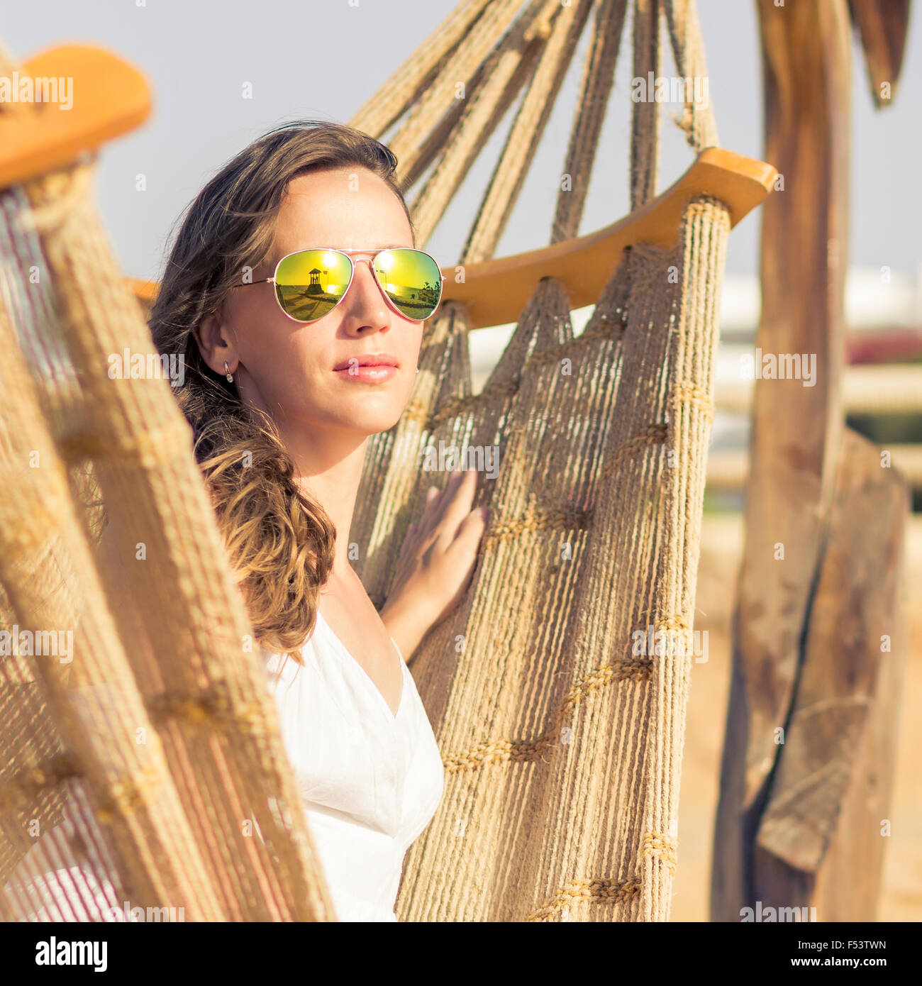 Young vacation woman in sunglasses relaxing at beach in hammock on summer holidays resort. - Stock Image